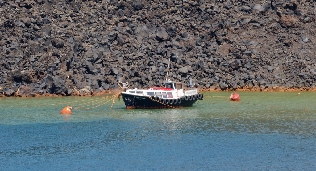 Boat in front of solidified basaltic lava